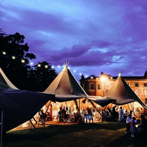 Three tipi set up at night with festoon lighting, open sides show wedding guests in Portstewart Northern Ireland