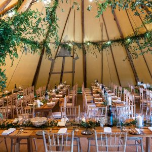 Inside a Tipi is decorated with tables and chairs, lush green foliage on the beam legs framing either side