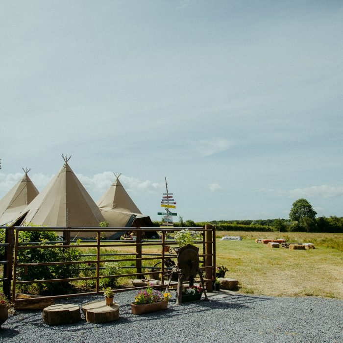 Three tipi wedding in a field, with a handmade wooden signpost and metal fencing in front