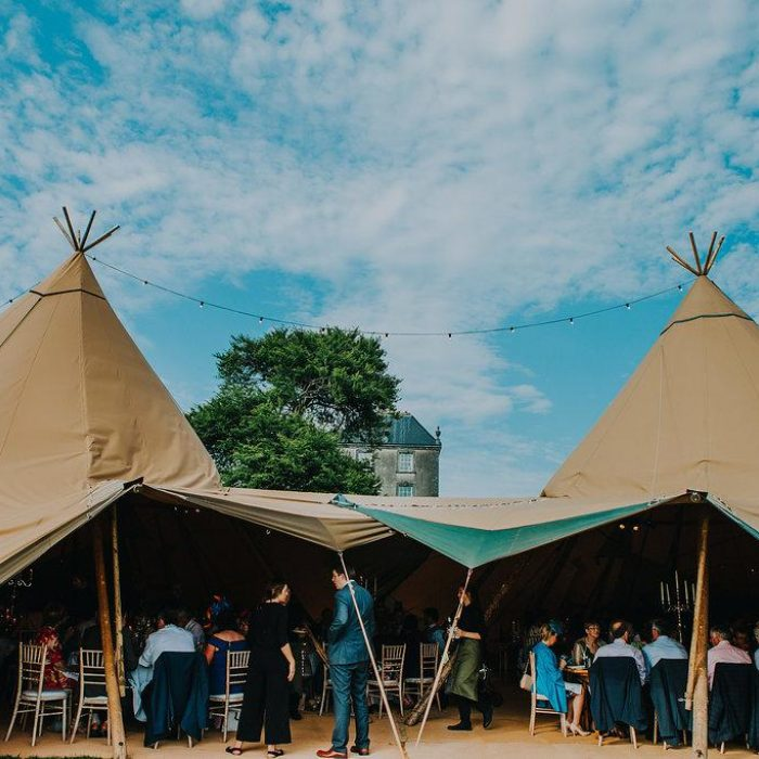 Open sided entrance to a five tipi wedding reception, inside is crowded with guests sitting at tables