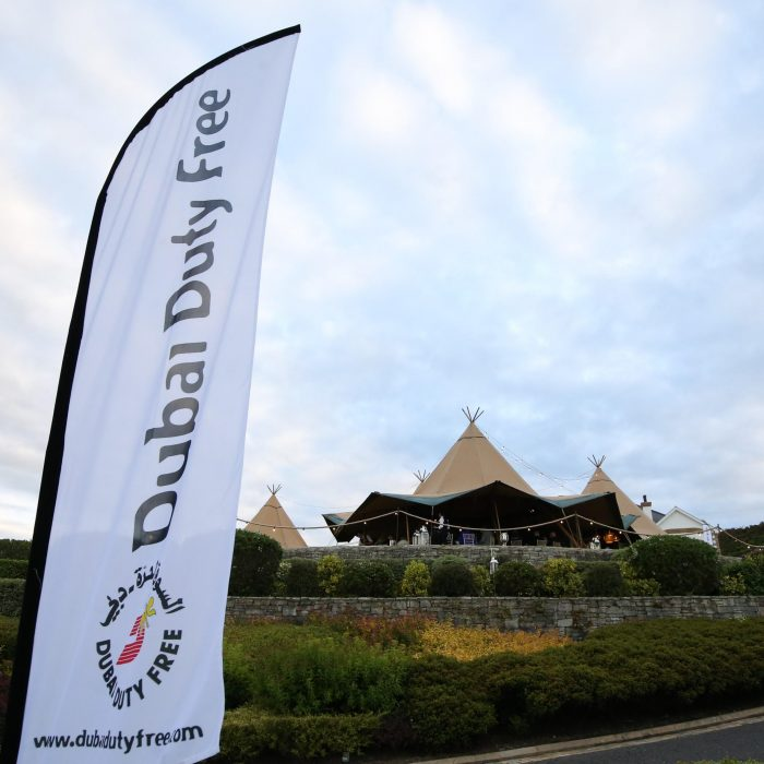 Tipi setup for Dubai Duty Free, corporate flag blows in the foreground with a three Tipi set up in the background