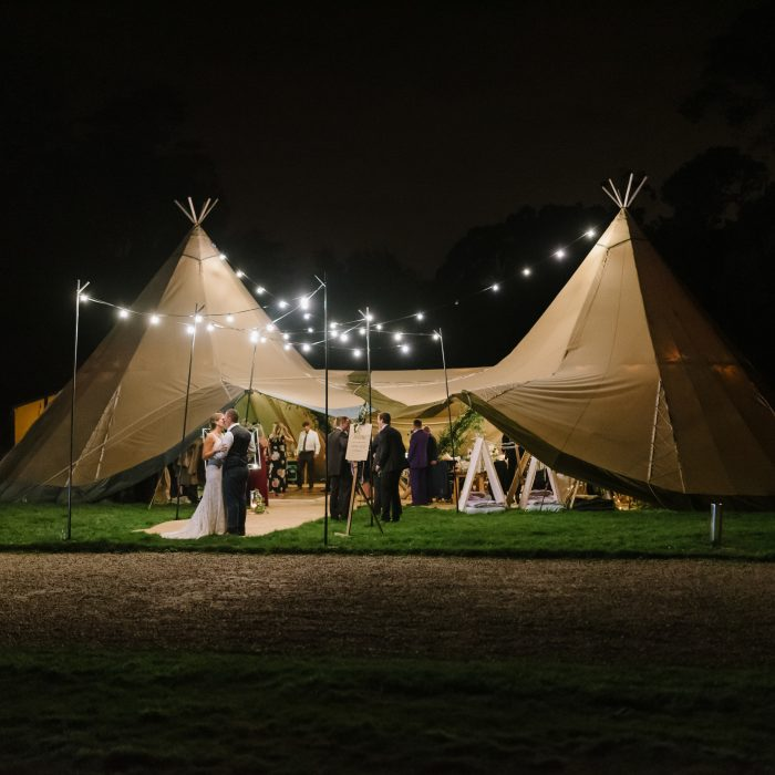 Bride & groom kiss under festoon lighting at night in the entrance of their tipi wedding reception