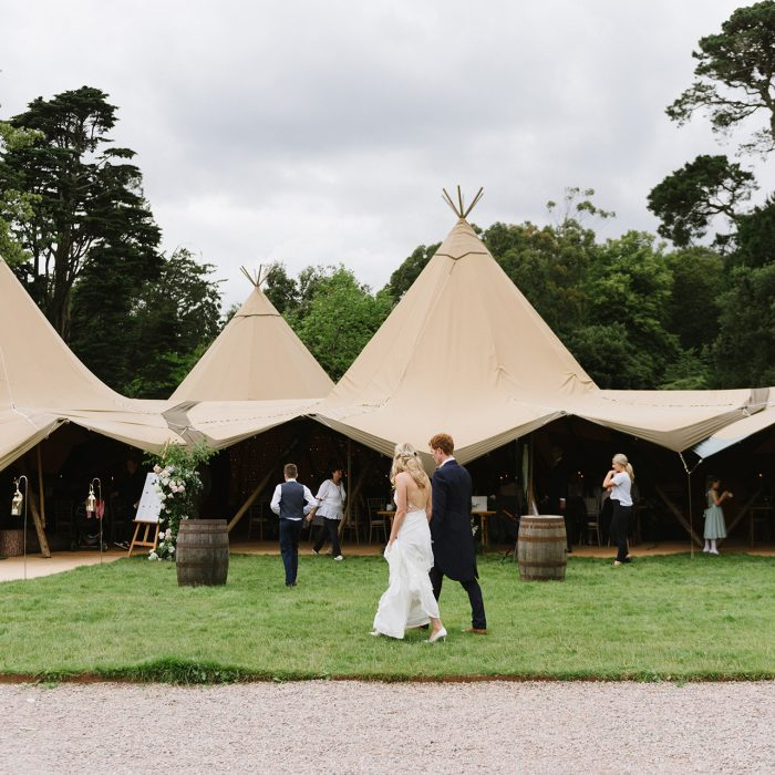 Bride & groom walk together in front of four linked tipis set up on the grounds of Mount Stewart