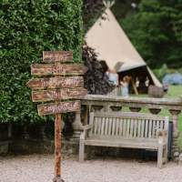 A wooden signpost stands beside a bench, a tipi peeks behind a hedge in the background