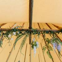 Fabulous green foliage, lilac and white florals hang from the crossbeams inside a Tipi