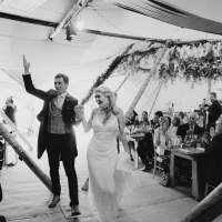 Bride and groom cheer as the walk through seated guests inside their wedding Tipi