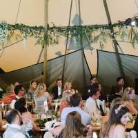 Guest sit and listen to a speech, foliage and flowers decorate the beams inside the wedding Tipi