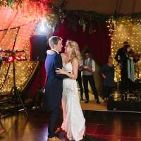 The bride and groom have their first dance inside their wedding Tipi, fairylit panels and a band are behind them
