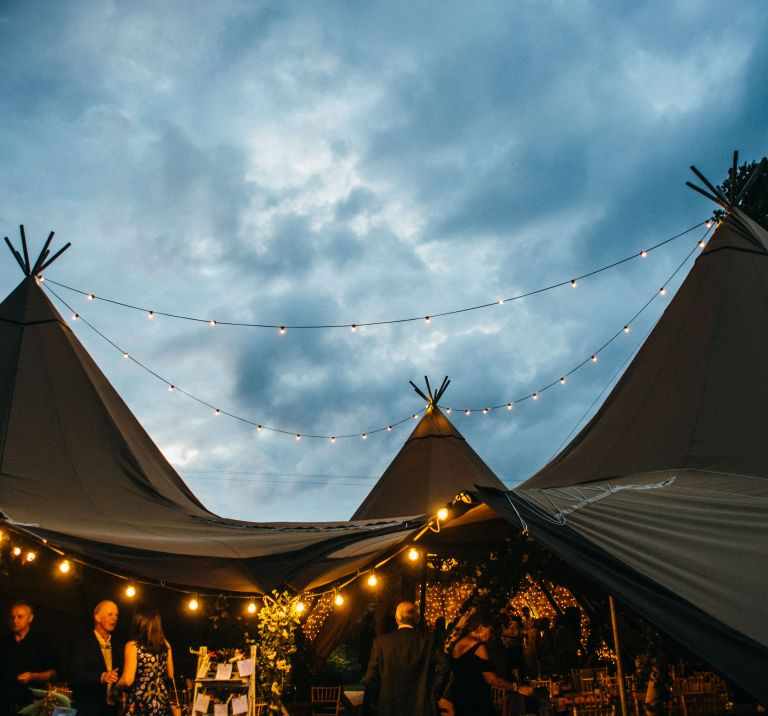 Three tipis are joined their central poles highlighted by the sky, festoon lighting hangs creating a cosy atmosphere