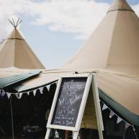 A blackboard easel welcomes guests to the wedding, Tipis sit behind it with bunting decorating the entrance