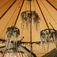 Three Hoops hang from the tipi roof, decorated with natural foliage, flowers and ribbons