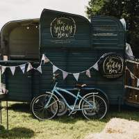 A horsebox champagne bar is decorated with bunting, a blue vintage bike sits in front and a drinks tray holding glasses