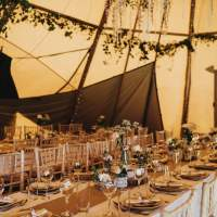 Tables and chairs sit in rows, with rustic decorations and natural foliage inside the Tipi