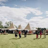 Guests stand outside talking with a four tipi Wedding reception on an open field, square hay-bales sit in front