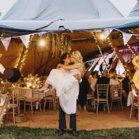 Groom holds the bride as they kiss at the entrance of a tipi decorated by bunting and Fox paper maché of themselves