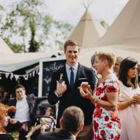 Guests chat and have fun outside the tipi wedding tents