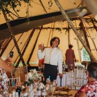 The groom smiles and holds his drink up in front of guests inside of the tipi wedding tent