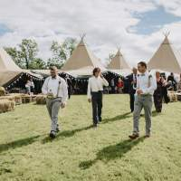The groom and groomsmen walk with the tipi wedding reception standing in the background