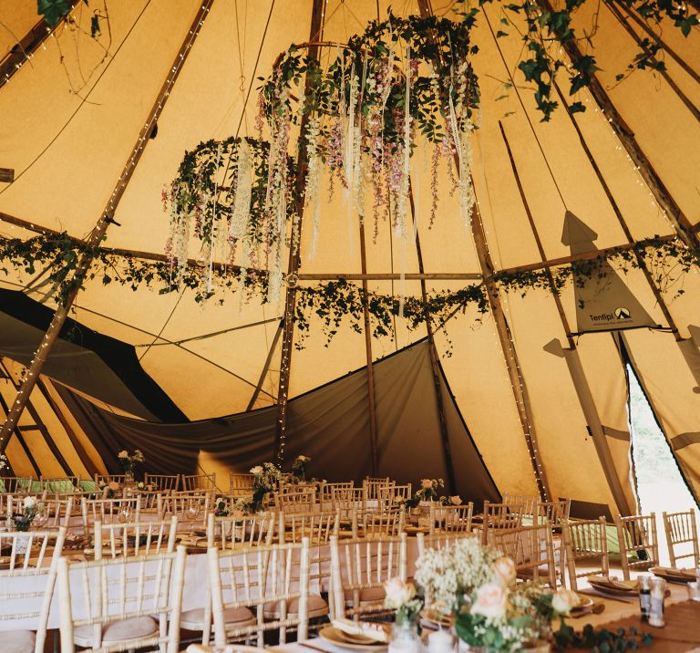 Inside Tipi decorated with natural foliage and hanging floral hoops
