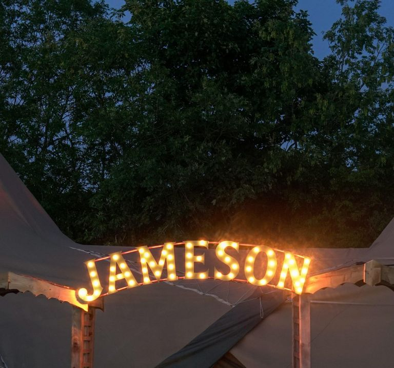 Two festival tipis stand with a double archway in front with Jameson light sign decorating the top