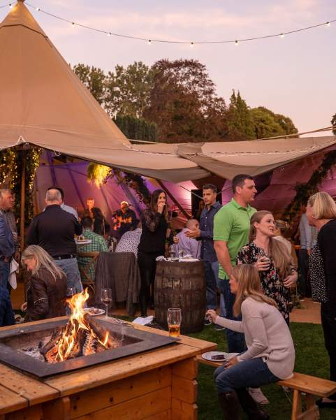 Corporate guests sit at a firepit and chat, open sided Tipis are behind them