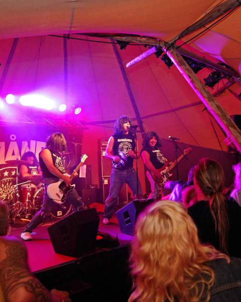 A rock band plays inside a festival tipi, crowds gather round the stage and it is lit up with purple lights