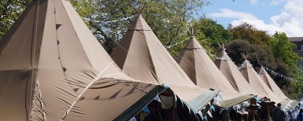 Six Tipi's line up at a food festival with colourful blue bunting decoration