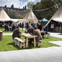 Tipis are joined in a ring, with bunting decoration, people sit at picnic benches in the foreground