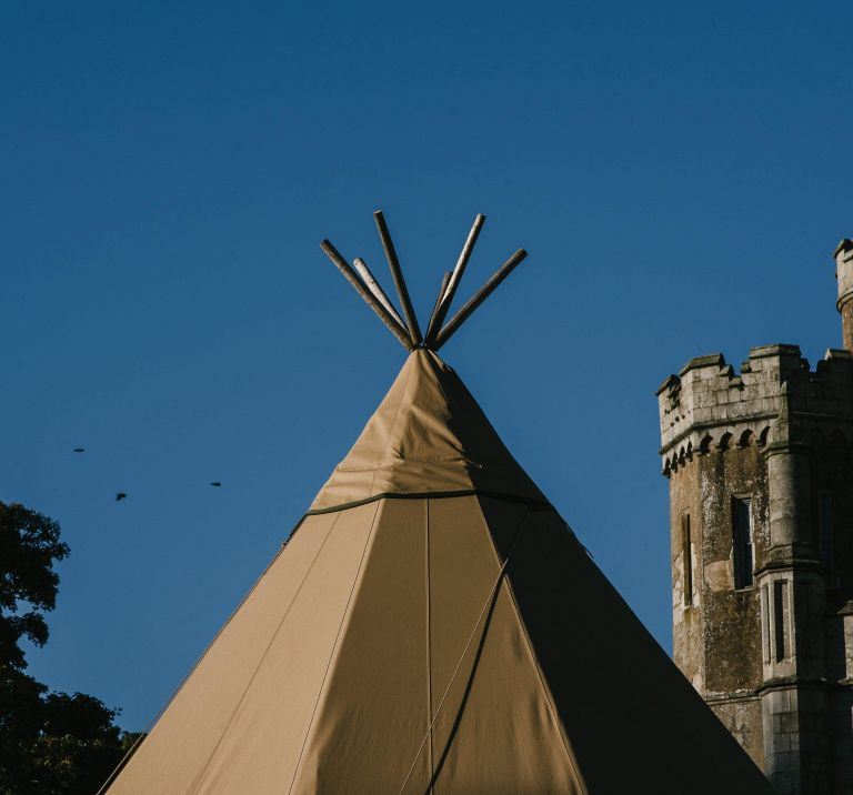 A top of a Tipi stands in front of Narrow Water Castle with a bright blue sky in the background
