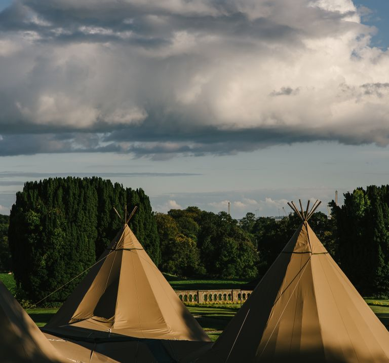 Three Tipis stand in the forefront with the grounds of Narrow Water Castle in the background and a cloudy bright sky