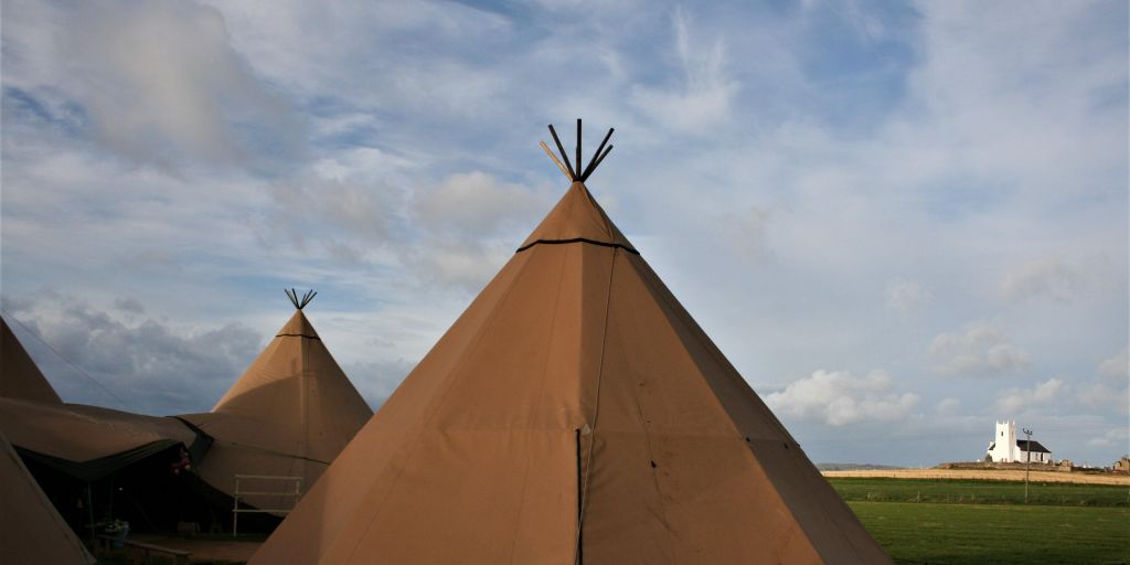 Tipi tops stand in front of a cloudy blue sky with a white church and green fields.