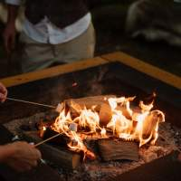 Wedding guests toast marshmallow over the top of magnakata's open firepits