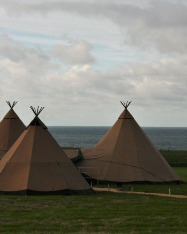 Four Tipis are joined together, overlapping canvases and festoon lighting, a bright blue cloudy sky is in the background