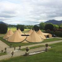 Six tipis are joined together in a doughnut formation in the grounds of a country estate