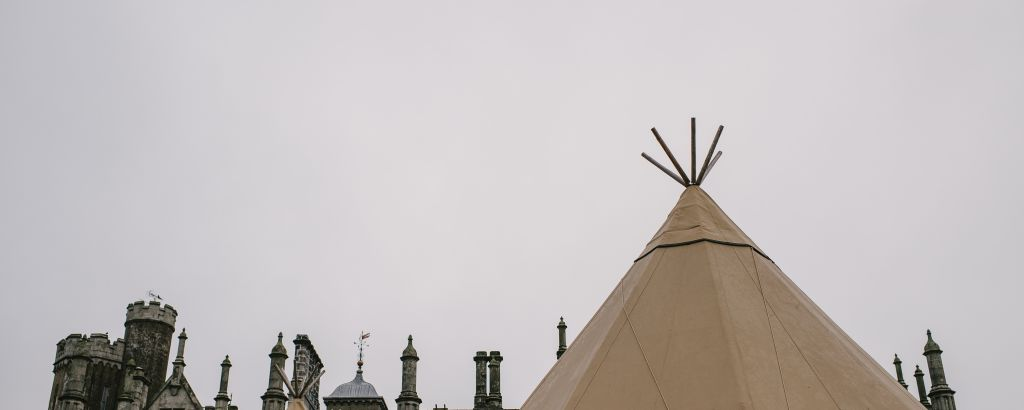 Two tipi tops are highlighted against a grey sky, the top of Narrow Water Castle stands behind them