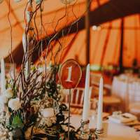 Rustic willow and flower centrepieces sit with a wooden table number