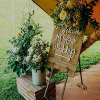A wooden sign saying welcome to our wedding sits on an easel, flower bouquets sit in metal buckets beside it