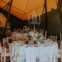 Round tables sit inside a tipi, decorated with silver candelabra and rustic flower centrepieces