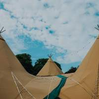 Three Tipis are joined together, overlapping canvases and festoon lighting, a bright blue cloudy sky is in the background