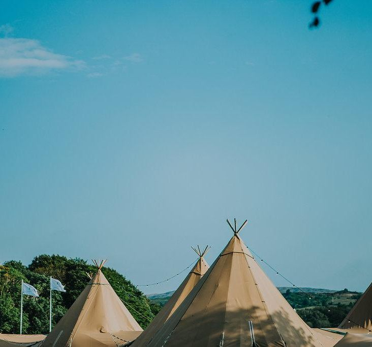 Five tipi tops against a bright blue sky, two blue flags stand in the background against trees