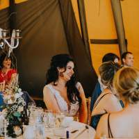 The bride sits smiling at a round table that has a silver candelabra centrepiece