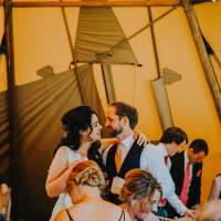 The bride and groom stand together with their arms around each other inside their tipi wedding reception