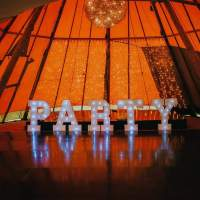 Large Lettered Lights spelling out Party stand in front of staging inside a tipi