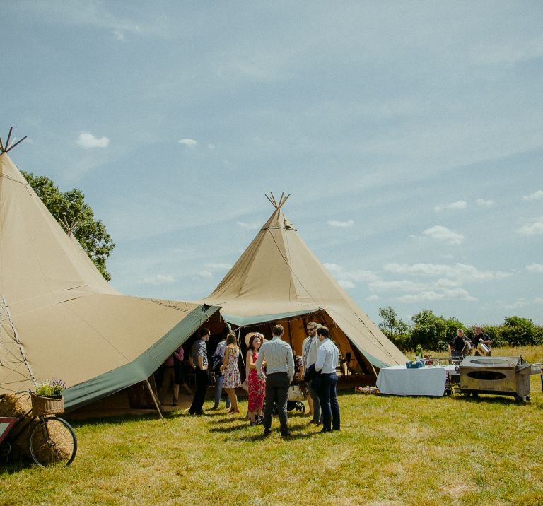 Guest arrive at a three tipi wedding set up, tables and bbq's stand outside beside the tipi entrance